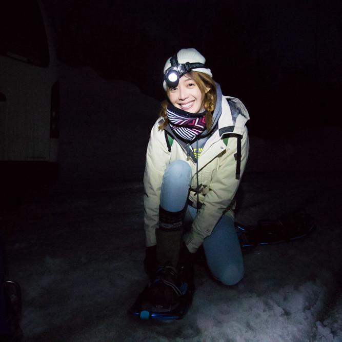 Puting on snowshoes at night