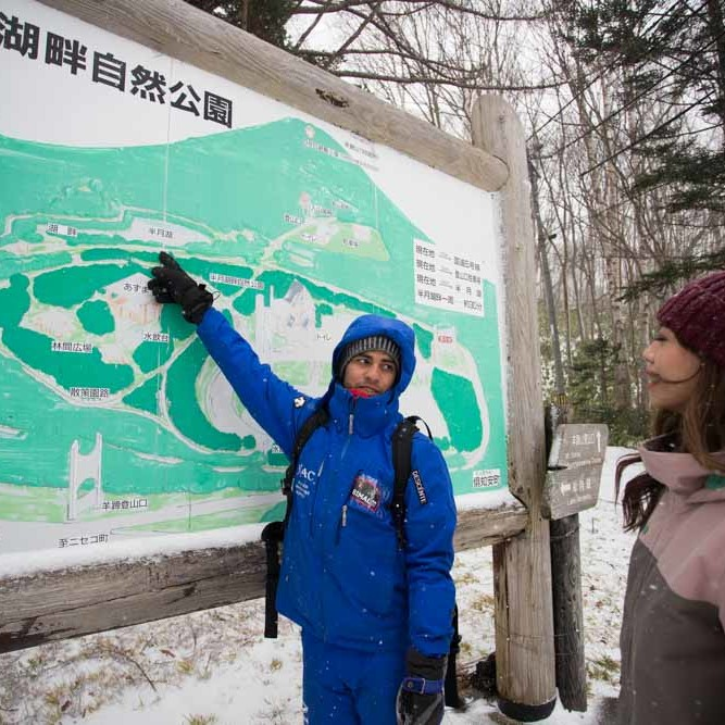 Snowshoe guide pointing at Niseko trail sign