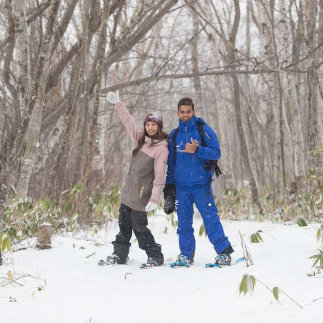 Two people snowshoeing in a Niseko forest